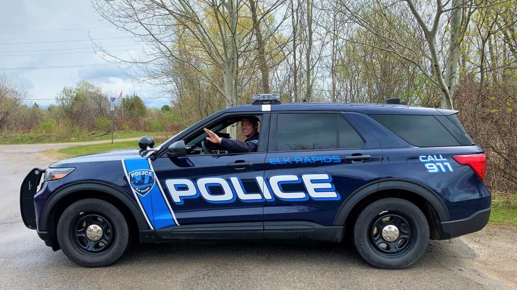 Elk Rapids Police Chief waving from patrol car.